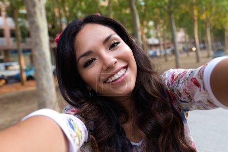 Photo pour Portrait extérieur de jolie étudiante prenant un selfie . - image libre de droit