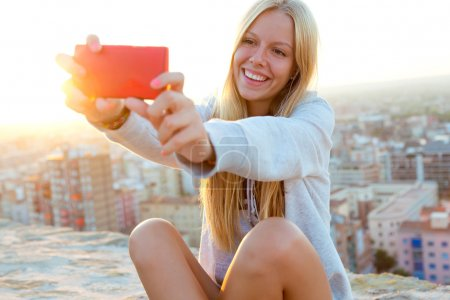 Beautiful blonde girl taking a selfie on the roof.