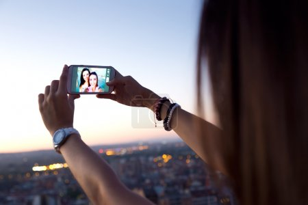 Beautiful girls taking a selfie on the roof at sunset.