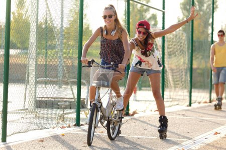 Photo for Outdoor portrait of group of friends with roller skates and bike riding in the park. - Royalty Free Image