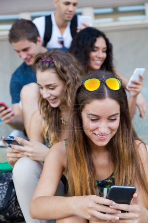 Photo for Portrait of group of students having fun with smartphones after class. - Royalty Free Image