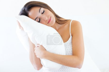Photo for Portrait of beautiful young woman holding a pillow and slepping on bed. - Royalty Free Image