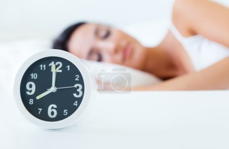Beautiful woman sleeping in bed trying to wake up with alarm clock.