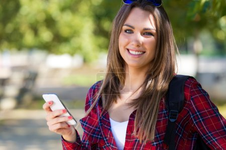 Photo for Outdoor portrait of beautiful girl using her mobile phone in city. - Royalty Free Image