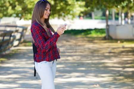 Portrait of beautiful girl using her mobile phone in city.