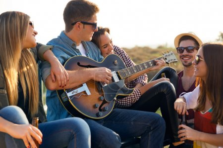 Photo pour Outdoor portrait of group of friends playing guitar and drinking beer. - image libre de droit
