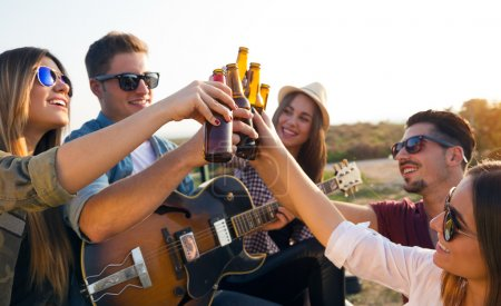 Photo pour Portrait de groupe d'amis de grillage avec des bouteilles de bière en plein air. - image libre de droit