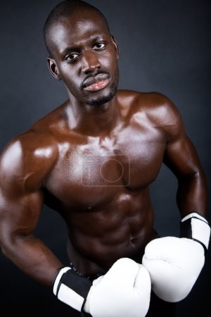 Young athletic boxer wearing gloves in black background.