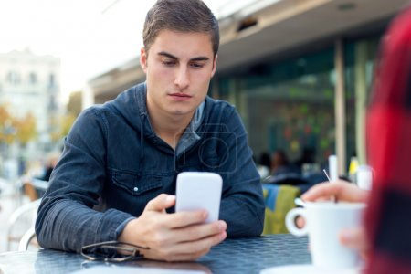 Young entrepreneur using his mobile phone at coffee shop.