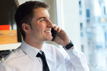 Young businessman using his mobile phone in office.
