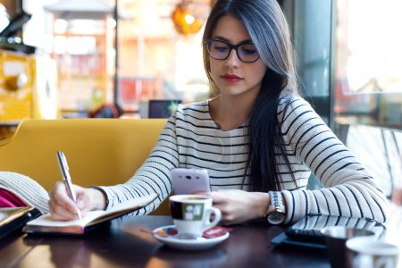 Photo for Portrait of young beautiful woman using her mobile phone in coffee. - Royalty Free Image