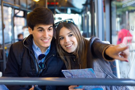 Young couple use their map and pointing where they want to go.