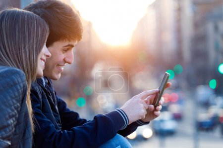 Photo pour Portrait of young couple of tourist in town using mobile phone. - image libre de droit