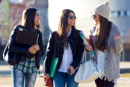 Photo pour Portrait de trois étudiantes marchant sur le campus de l'université . - image libre de droit