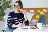 Confident young woman working in her office with mobile phone.