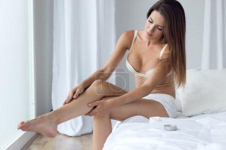 Pretty young woman applying body cream on legs.