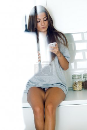 Beautiful young woman drinking coffee and using her mobile phone
