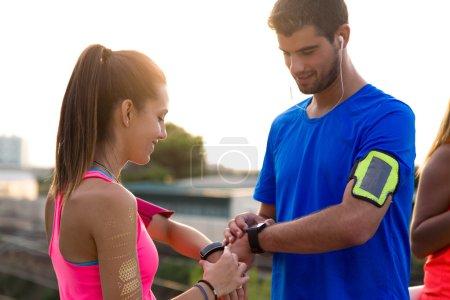 Photo pour Portrait extérieur de jeune couple en utilisant ils smartwatch après avoir couru . - image libre de droit