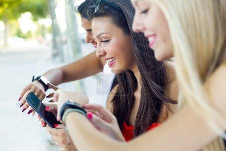 Photo pour Portrait de trois filles, bavardant avec leurs smartphones au parc en plein air. - image libre de droit