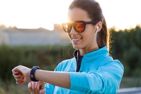 Photo pour Portrait extérieur de jeune femme en utilisant ils smartwatch après avoir couru . - image libre de droit
