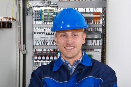 Photo pour Portrait d'un joyeux jeune électricien masculin debout devant Fusebox - image libre de droit