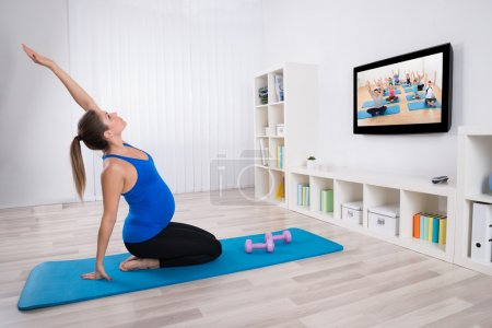 Photo for Young Pregnant Woman Exercising In Front Of Television At Home - Royalty Free Image