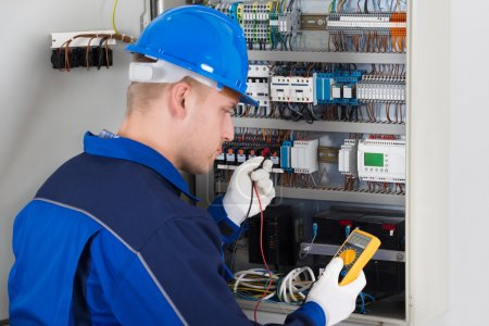 Photo pour Beau technicien masculin examinant Fusebox avec testeur de résistance d'isolation numérique - image libre de droit