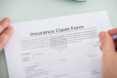 Photo for Close-up Of A Male Hand Over Insurance Claim Form - Royalty Free Image