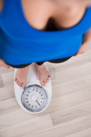Photo for High Angle View Of Woman Measuring Body Weight On Weighing Scale - Royalty Free Image