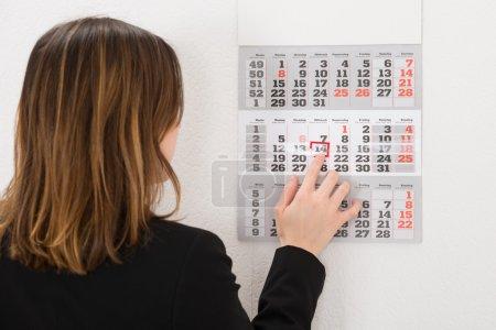 Photo pour Jeune femme d'affaires plaçant la marque rouge sur la date de calendrier - image libre de droit