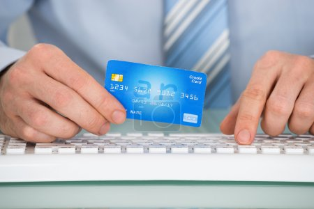 Businessperson With Credit Card And Keyboard
