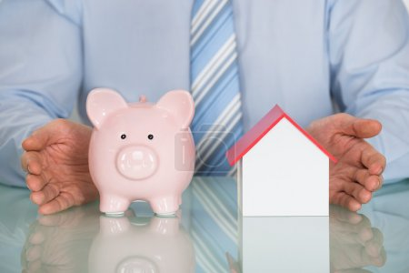 Photo for Close-up Of Businessman Protecting Piggy Bank And House Model - Royalty Free Image