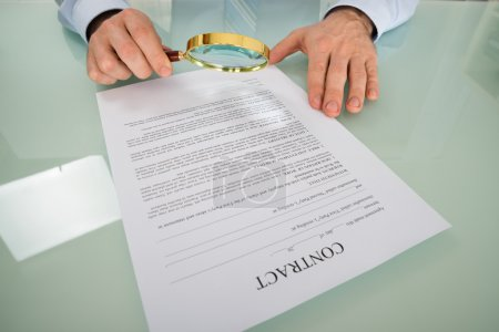 Person's Hand Looking At Contract