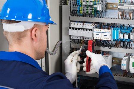 Foto de Foto de primer plano de hombre electricista reparación de caja de fusibles - Imagen libre de derechos