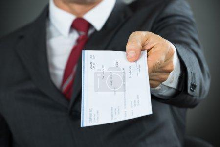 Photo pour Gros plan d'un homme d'affaires qui remet un chèque en mains propres au bureau - image libre de droit