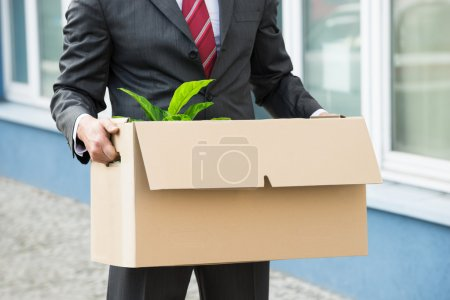 Photo for Close-up Photo Of Unemployed Businessperson Carrying Cardboard Boxes - Royalty Free Image