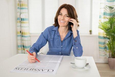 Photo pour Heureuse jeune femme caucasienne tenant le journal tout en parlant sur portable au bureau - image libre de droit