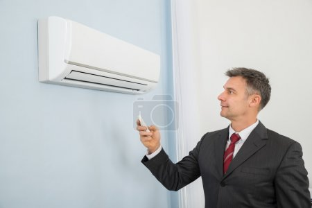 Photo for Mature Happy Caucasian Businessman Using Remote Control To Operate Air Conditioner - Royalty Free Image