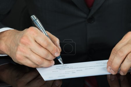 Businessman Filling Blank Cheque
