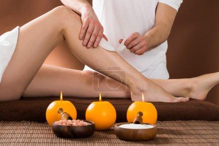 Photo pour Gros plan d'une jeune femme se faisant épiler les jambes en appliquant des bandes de cire au Beauty Spa - image libre de droit