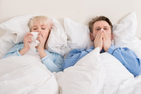 Couple Blowing Their Nose While Lying In Bed