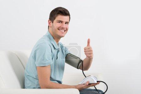 Happy Man Measuring Blood Pressure