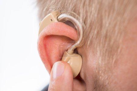 Photo pour Photo de gros plan d'un homme portant la prothèse auditive dans l'oreille - image libre de droit