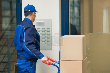 Photo for Mature Delivery Man With Trolley Full Of Box Using Security To Enter Building - Royalty Free Image