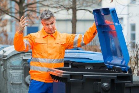 Photo pour Malheureux mature mâle rue nettoyeur regardant dans poubelle - image libre de droit