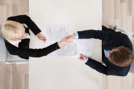Businesspeople Shaking Hand At Desk