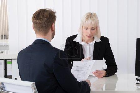 Photo pour Jeune femme d'affaires discuter au CV avec un candidat masculin au bureau - image libre de droit