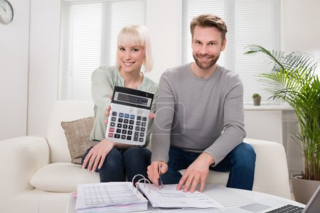 Photo for Happy Couple Showing Calculator While Analyzing Bill - Royalty Free Image