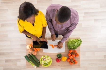 Photo pour Vue élevée du jeune couple dans la cuisine à l'aide d'une tablette numérique - image libre de droit