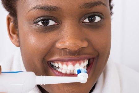 Photo pour Gros plan d'une femme africaine se brossant les dents avec une brosse à dents électrique - image libre de droit
